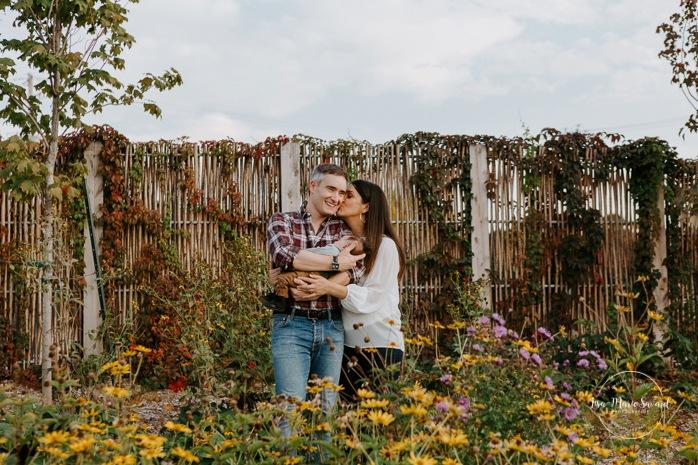 Outdoor lifestyle newborn session. Parents holding baby and kissing in front of flowers. Parc Pierre-Dansereau. Photo de bébé à domicile à Montréal. Montreal in-home baby session. Photographe de bébé à Montréal. Montreal baby photographer.