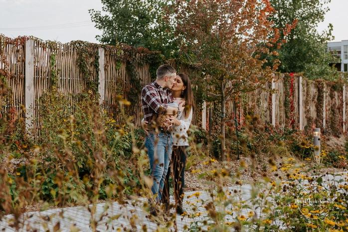 Outdoor lifestyle newborn session. Parents holding baby and kissing in front of flowers. Parc Pierre-Dansereau. Séance nouveau-né lifestyle à Outremont. Outremont lifestyle newborn session. Photographe de nouveau-né à Montréal. Montreal newborn photographer.