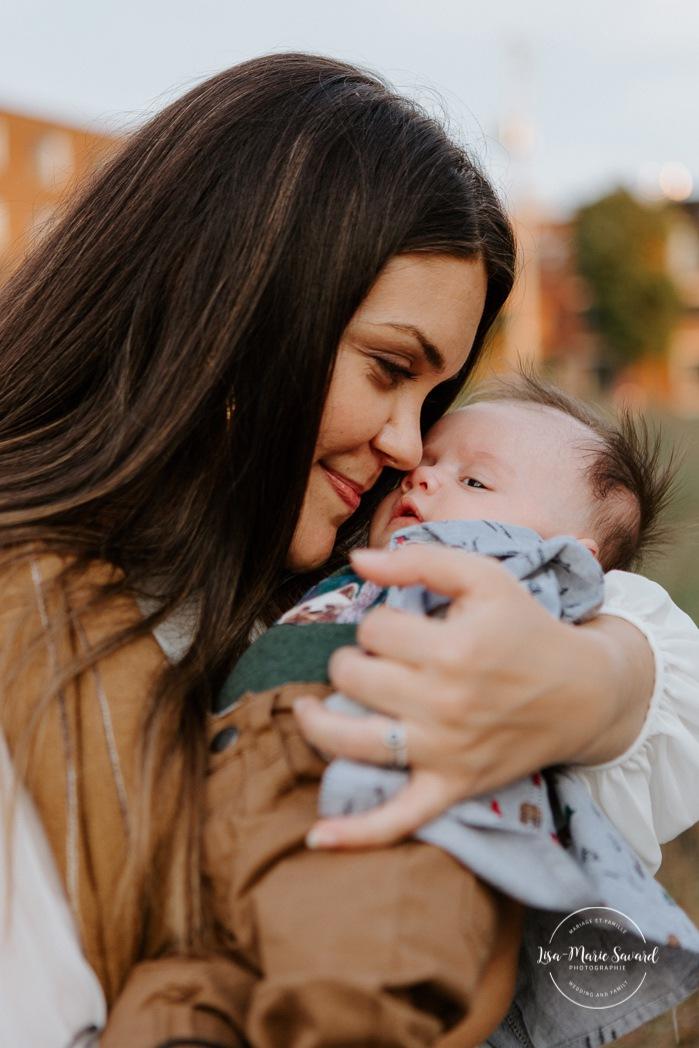 Outdoor lifestyle newborn session. Mom holding baby boy closely. Parc Pierre-Dansereau. Photo de bébé à domicile à Montréal. Montreal in-home baby session. Photographe de bébé à Montréal. Montreal baby photographer.