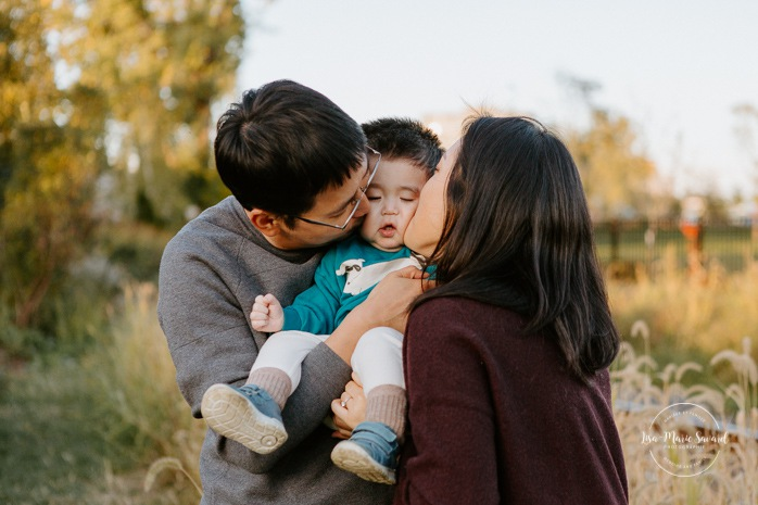Fall family photos. Fall family session. Parents kissing baby on cheek. Korean family photos. Séance photo le long du Canal Lachine. Lachine Canal photoshoot. Photos de famille Canal Lachine. Lachine Canal family photos. Photographe de famille à Montréal. Montreal family photographer.