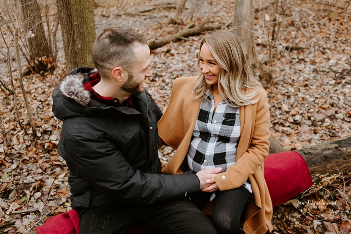 Winter maternity photos without snow. Maternity session in forest. Couple sitting on fallen tree. Photographe à Ville-Émard. Montreal Southwest maternity photos.