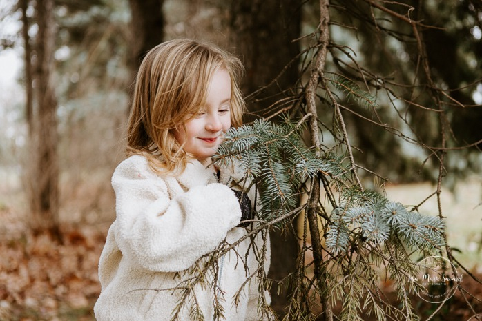 Young girl smelling pine tree. Winter maternity photos without snow. Maternity photos with child. Maternity photos with sibling. Photographe à Ville-Émard. Montreal Southwest maternity photos.