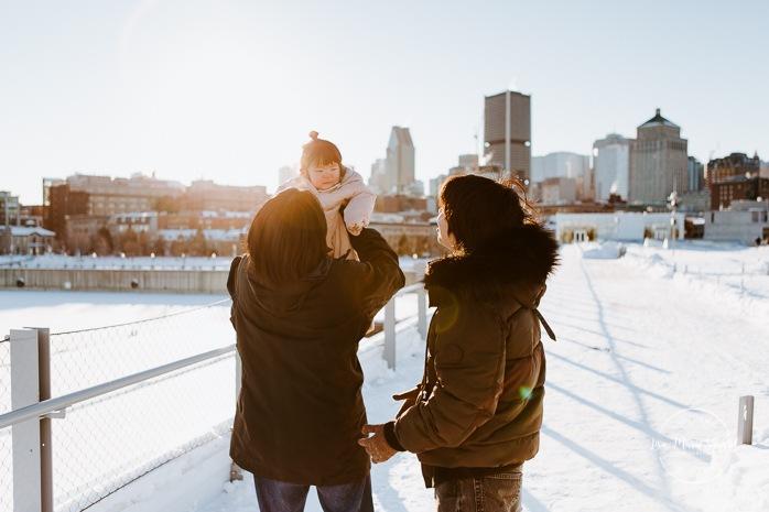 Winter family session. Family photos in the snow. Asian family photos. Family photos cityscape. Skyline family photos. Séance photo dans le Vieux-Port de Montréal. Photos de famille à Montréal. Grand Quai de Montréal. Promenade d'Iberville. Old Port of Montreal photo session. Montreal family photos.