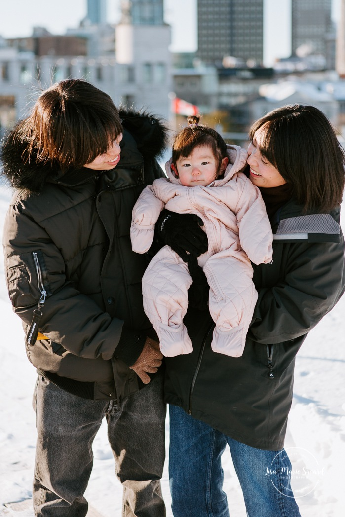 Winter family session. Family photos in the snow. Asian family photos. Family photos cityscape. Skyline family photos. Photos de famille à Montréal. Grand Quai de Montréal. Promenade d'Iberville. Montreal family photos.