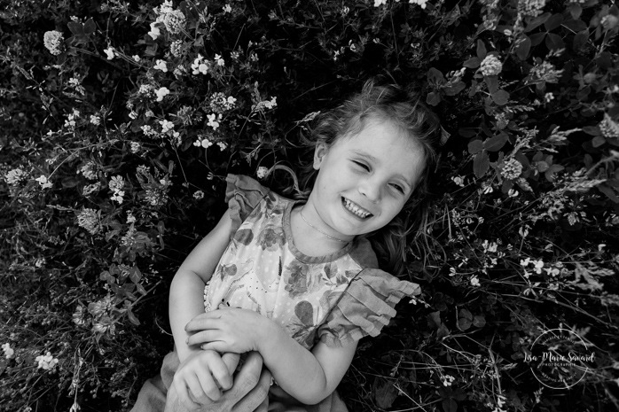 Girl lying down in grass wild flowers. Summer family photos. Golden hour family session. Family photos with toddler girl. Parc de la Promenade Bellerive. Photographe de famille à Montréal. Montreal family photographer.